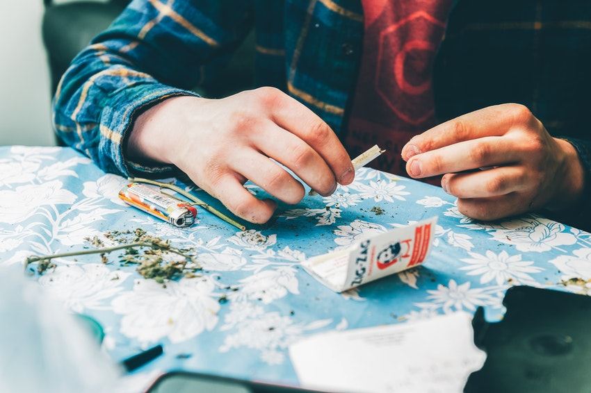 Man in Flannel Shirt Preparing to Roll Joint at Kitchen Table Using Zig Zag Rolling Papers