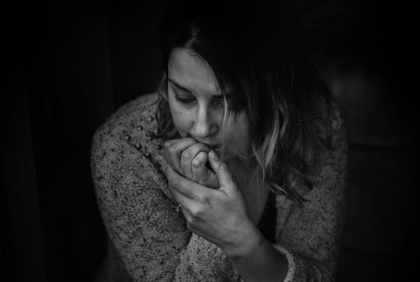 Nervous woman biting nails to alleviate anxiety