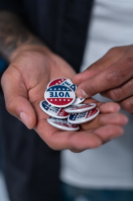 Hand holding 'VOTE' pins to give to millennial voters at polling center