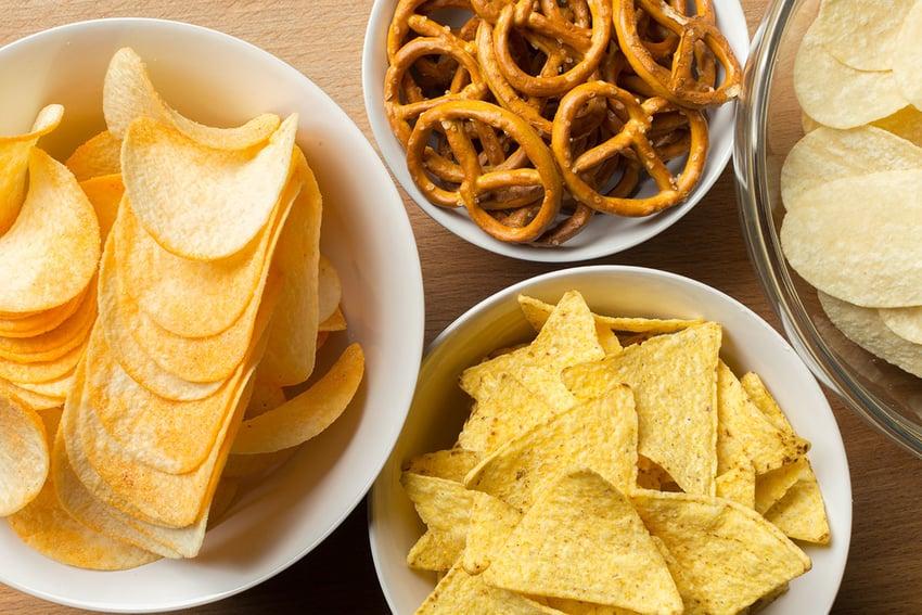 Bowls of pretzels, Pringles, Lays and corn chips