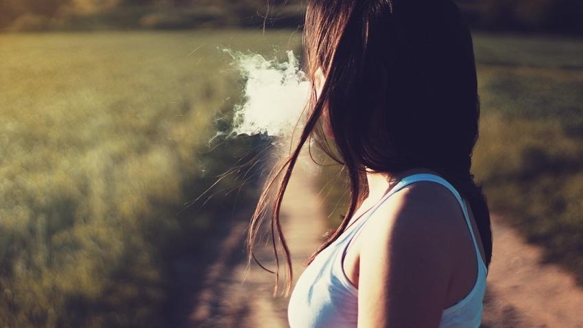 Woman facing away from camera and exhaling vaporizer cloud