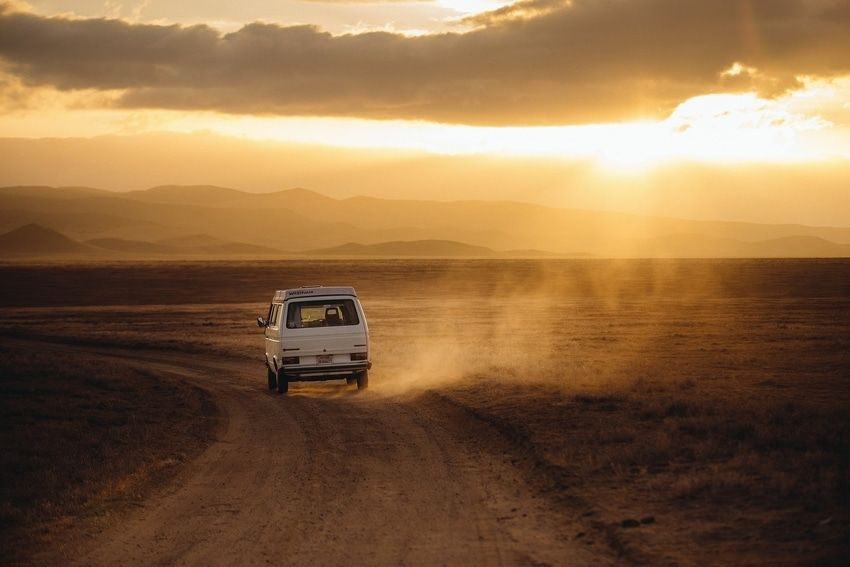 Volkswagon van driving down dusty road at sunset on road trip toward popular cannabis culture destination