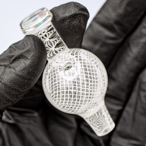 Black gloved hand holding Mycomann engraved glass bubble cap with opal handle.