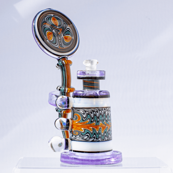 Multicolored dab rig with lavender base, striped neck, moonstone accents, and swirled design on chamber and mouthpiece.