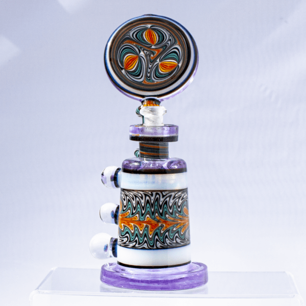 Hedman Headies dab rig with lavender base, moonstone accents, and swirled, multicolored design on chamber and mouthpiece.