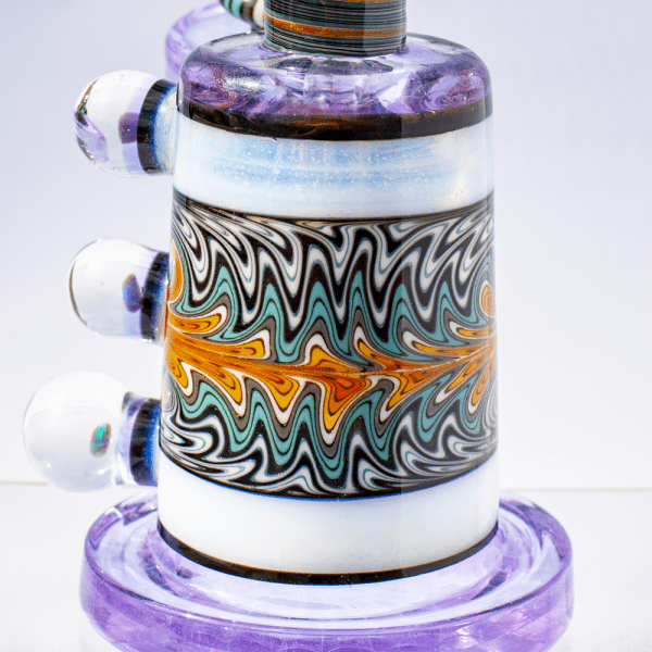 Closeup of multicolored dab rig by Hedman Headies showing intricately swirled chamber design, lavender base and opal accents.