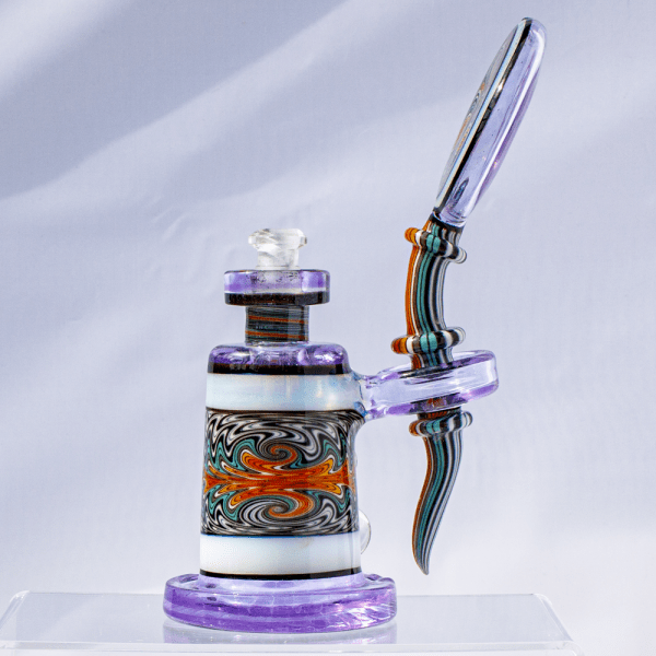 Side view of Hedman Headies dab rig displaying multicolored striped stem and intricately swirled glass chamber design.