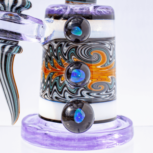 Closeup of color-changing moonstone accents, intricately colored chamber and lavender base on dab rig by Hedman Headies.