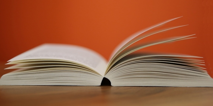 Book of terminology open on table beside bright orange wall