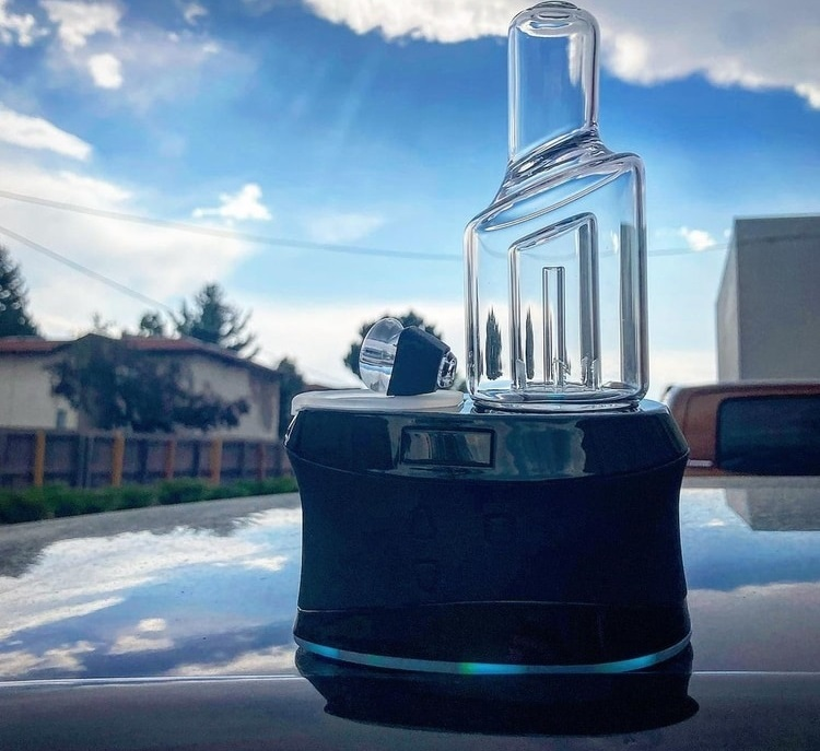 High Five Duo Dry Herb Vaporizer on hood of car outdoors under cloudy sky