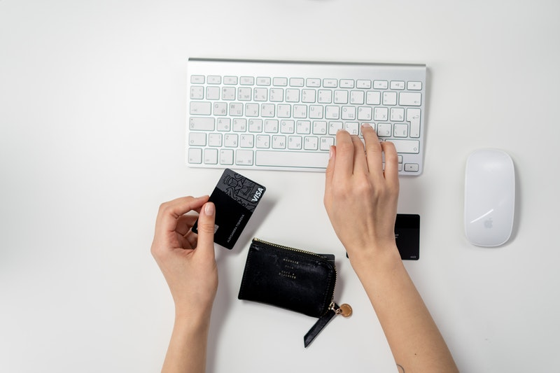 Right hand of online shopper typing while left hand holds black credit card beside wallet and computer mouse