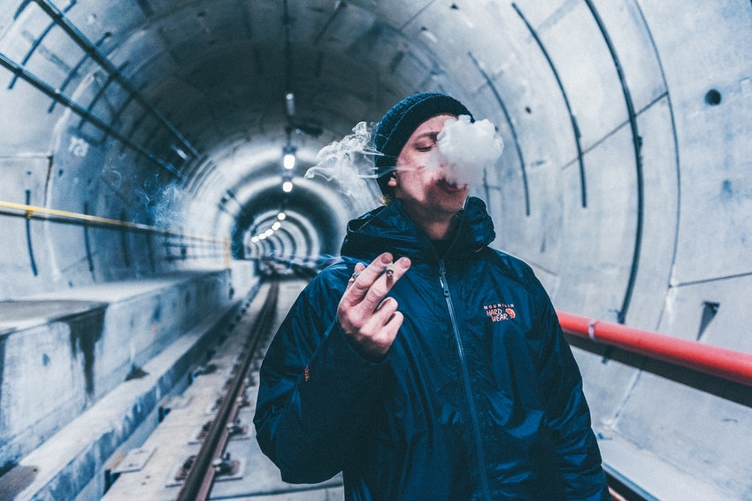 Smoker holding cigarette and exhaling smoke cloud