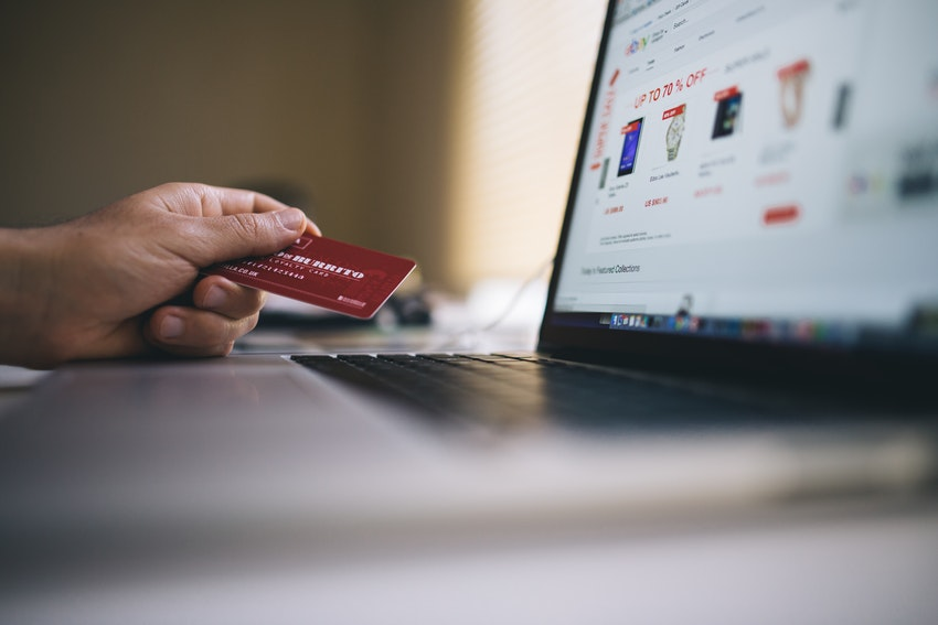 Online shopper using credit card and laptop to order products